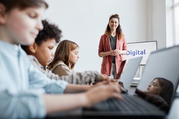 Portret uśmiechniętej nauczycielki z grupą dzieci korzystających z komputerów podczas lekcji informatyki w szkole
