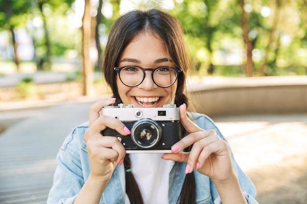 Portret uśmiechniętej optymistycznej szczęśliwej słodkiej młodej studentki w okularach, siedzącej na ławce na zewnątrz w parku przyrody, trzymającej kamerę
