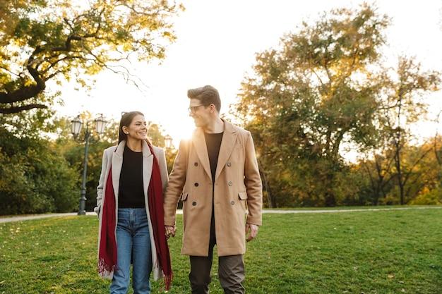 Portret uśmiechniętej pary mężczyzny i kobiety w wieku 20 lat, patrzących na siebie i spacerujących w jesiennym parku