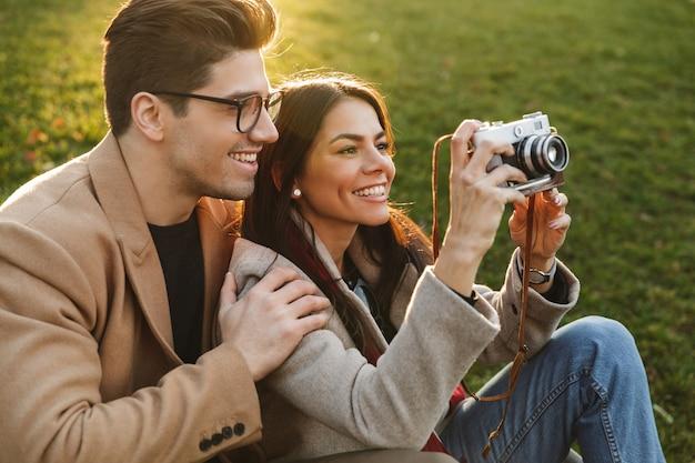 Portret uśmiechniętej pary mężczyzny i kobiety w wieku 20 lat robiących zdjęcie na retro aparacie, siedząc na trawie w parku