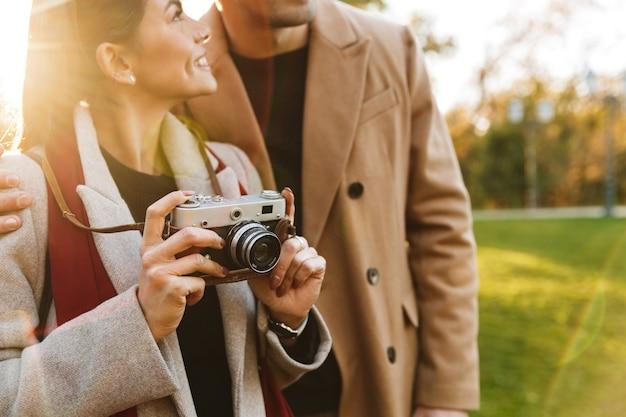 Portret uśmiechniętej pary mężczyzny i kobiety w wieku 20 lat za pomocą zabytkowego aparatu podczas spaceru w jesiennym parku