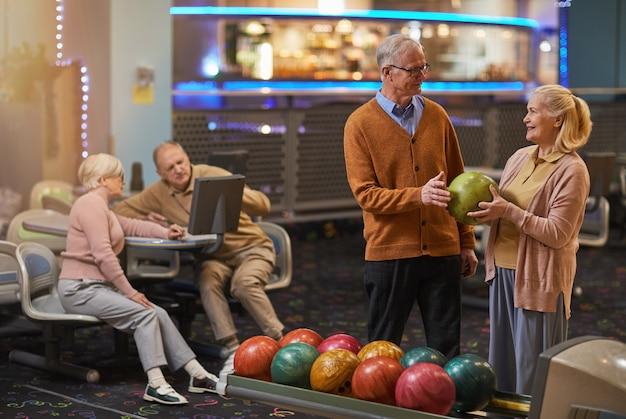Portret uśmiechniętej pary seniorów grającej w kręgle razem z przyjaciółmi w tle, ciesząc się aktywną rozrywką w kręgielni, kopia przestrzeń