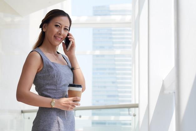 Portret uśmiechniętej, pewnej siebie, młodej bizneswoman azjatyckiej pijącej kawę i rozmawiającej przez telefon komórkowy w biurze