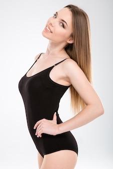 Portret uśmiechniętej, pewnej siebie, pięknej, atrakcyjnej, szczupłej młodej kobiety w czarnym stroju kąpielowym na białej ścianie