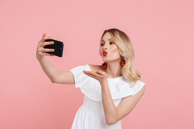 Portret uśmiechniętej pięknej blondynki w letniej sukience stojącej na białym tle nad różowym, robiącej selfie, wysyłającej buziaka