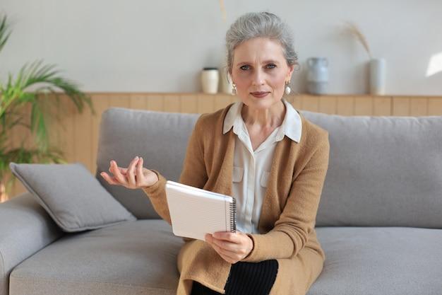 Portret uśmiechniętej, pięknej kobiety w średnim wieku, patrzącej w kamerę, wykonującej wideorozmowę, rozmowę o pracę lub randkowanie online.