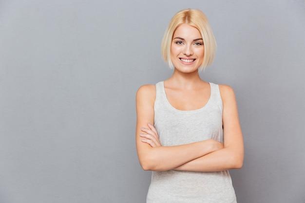 Portret uśmiechniętej pięknej młodej kobiety stojącej z rękami skrzyżowanymi na szarej ścianie