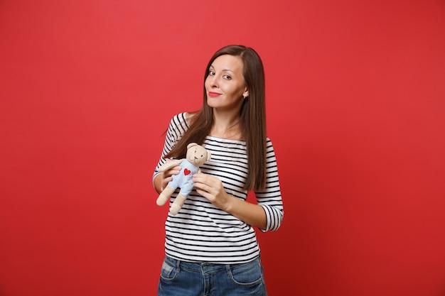 Portret uśmiechniętej pięknej młodej kobiety w swobodnych ubraniach w paski, trzymającej pluszową zabawkę pluszowego misia