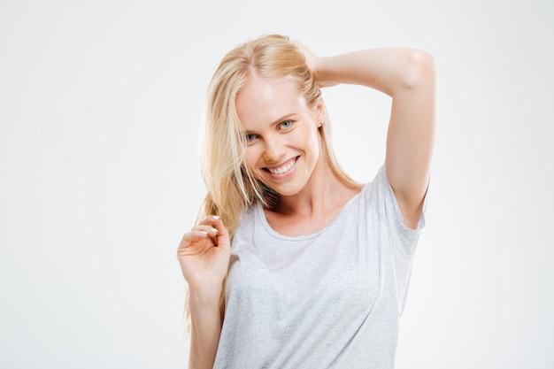 Portret uśmiechniętej pięknej młodej kobiety z blond włosami nad białą ścianą