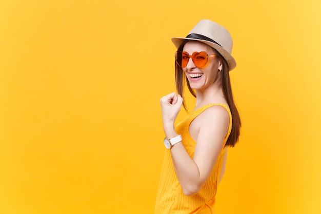 Portret uśmiechniętej podekscytowanej młodej kobiety w słomkowym letnim kapeluszu, pomarańczowe okulary robiące gest zwycięzcy, mówiące tak na białym tle na żółtym tle. koncepcja życia szczere emocje ludzi. powierzchnia reklamowa.