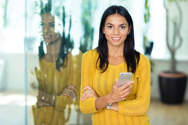 Portret uśmiechniętej przypadkowej bizneswoman trzymającej smartfon w biurze