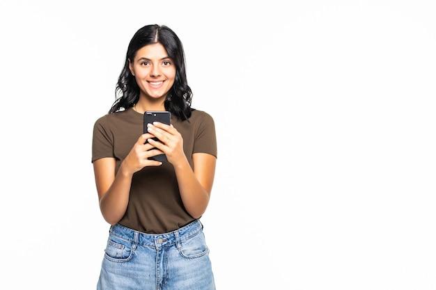 Portret uśmiechniętej przypadkowej kobiety trzymającej smartfon nad białą ścianą