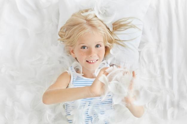 Portret uśmiechniętej radosnej dziewczynki rasy kaukaskiej o jasnych włosach i piegach bawiącej się białymi piórami leżąc w łóżku, z figlarnym, wesołym wyrazem swojej ładnej dziecięcej twarzy
