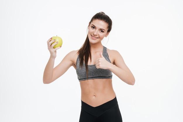 Portret uśmiechniętej radosnej kobiety fitness trzymającej jabłko i pokazującej kciuki na białym tle