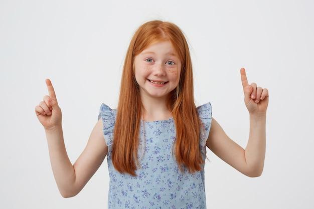 Portret uśmiechniętej rudowłosej dziewczyny z drobnymi piegami, patrzy w kamerę, wskazuje na przestrzenie kopii, nosi bluet, stoi na białym tle.