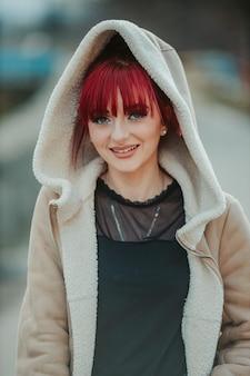 Portret uśmiechniętej rudowłosej kobiety z grzywką w ciepłym płaszczu zimowym