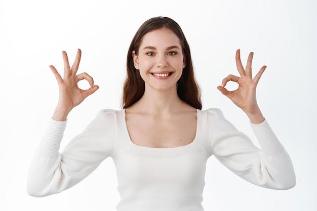 Portret uśmiechniętej ślicznej studentki pokazującej jej aprobatę, w porządku, w porządku, gest, robiąc znaki ok i kiwając głową, chwaląc i polecając przedmiot, stojąc zadowolona na białej ścianie