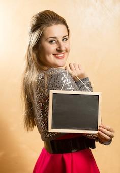 Portret uśmiechniętej słodkiej kobiety trzymającej małą tablicę