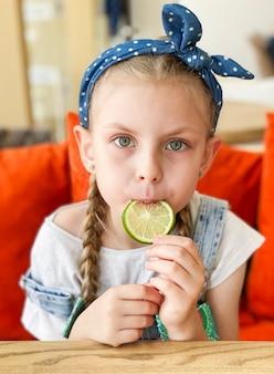Portret uśmiechniętej słodkiej małej dziewczynki trzymającej plasterki limonki