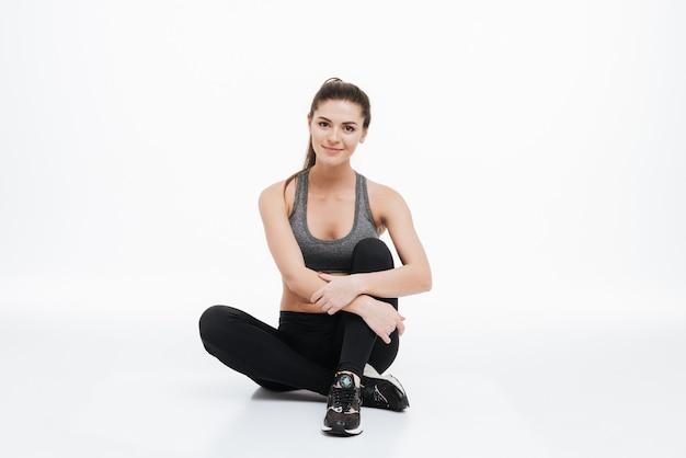 Portret uśmiechniętej sportowej kobiety siedzącej na podłodze ze skrzyżowanymi nogami i rękami na białym tle