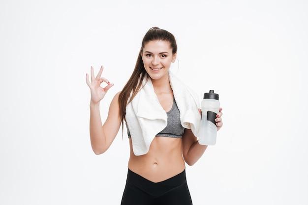 Portret uśmiechniętej sportowej kobiety trzymającej butelkę wody i wykonującej dobry gest, patrząc na przód