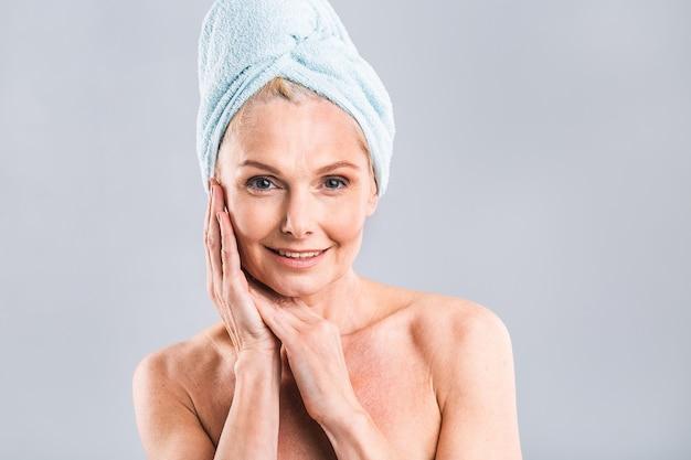 Portret uśmiechniętej starszej kobiety czującej miękką skórę dłonią po kąpieli w spa dojrzała kobieta owinięta ręcznikiem na ciele i mokrych włosach patrząc na kamerę