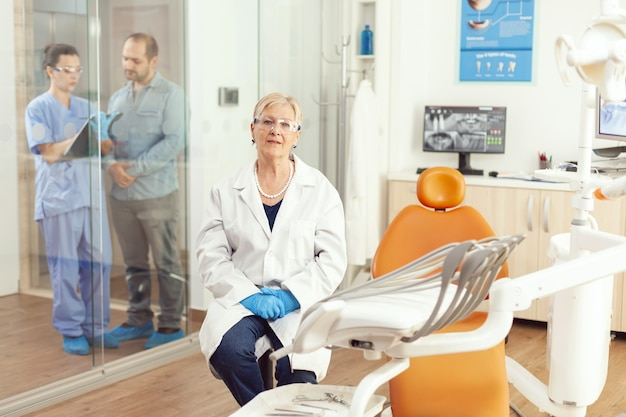 Portret uśmiechniętej starszej kobiety dentysty w gabinecie stomatologicznym, podczas gdy pielęgniarka medyczna rozmawia z pacjentem w tle