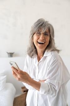 Portret uśmiechniętej starszej kobiety korzystającej z telefonu komórkowego w domu
