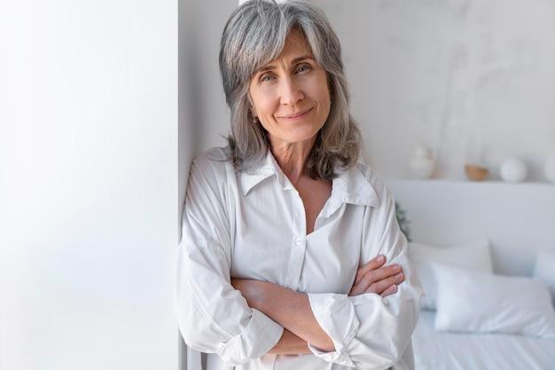 Portret uśmiechniętej starszej kobiety relaksującej się w domu