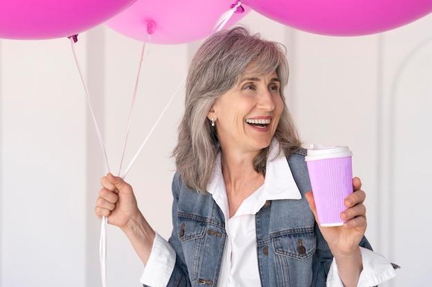 Portret uśmiechniętej starszej kobiety trzymającej filiżankę i różowe balony