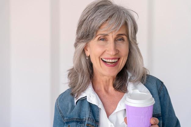 Portret uśmiechniętej starszej kobiety trzymającej filiżankę