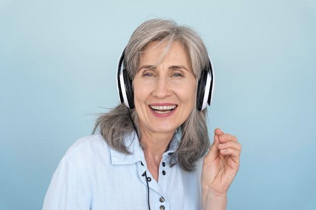 Portret uśmiechniętej starszej kobiety używającej słuchawek