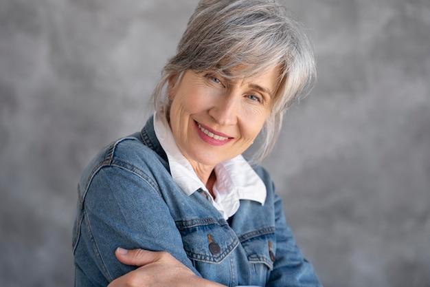 Portret uśmiechniętej starszej kobiety w dżinsowej kurtce