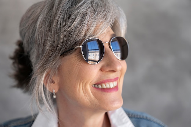Portret uśmiechniętej starszej kobiety w okularach przeciwsłonecznych
