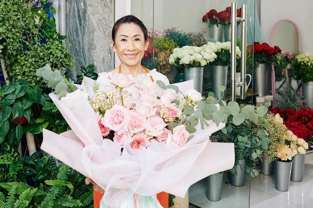 Portret uśmiechniętej starszej właścicielki kwiaciarni stojącej z dużym jasnoróżowym bukietem, który stworzyła dla klienta