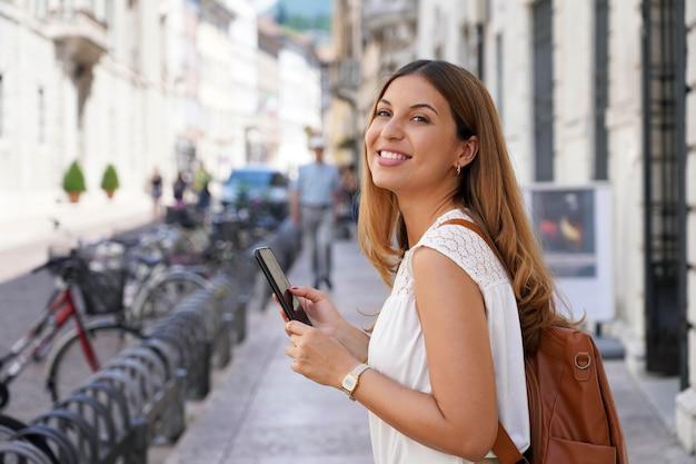 Portret uśmiechniętej studentki korzystającej ze smartfona spacerującej po ulicy miasta