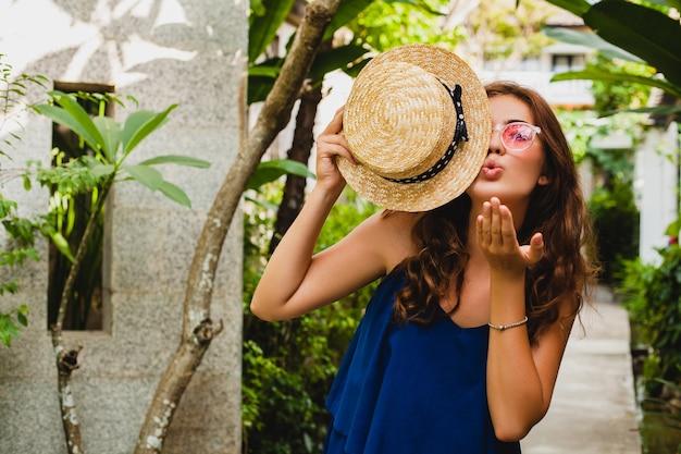 Portret uśmiechniętej szczęśliwej atrakcyjnej młodej kobiety w niebieskiej sukience i słomkowym kapeluszu w różowych okularach przeciwsłonecznych spacerującej w tropikalnym hotelu willi spa na wakacjach w letnim stroju