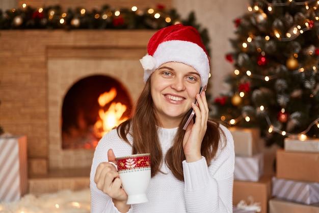 Portret uśmiechniętej, szczęśliwej kobiety rozmawia przez telefon, siedząc w przytulnym pokoju z kominkiem i choinką, patrząc w kamerę z pozytywnym wyrazem twarzy, delektując się gorącą kawą lub herbatą.
