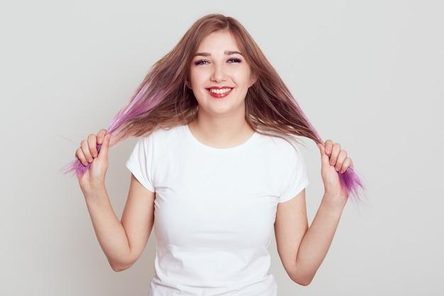 Portret uśmiechniętej, szczęśliwej kobiety w młodym wieku, patrzącej na kamerę z zębatym uśmiechem, odciągającej włosy na bok, ma zabawny wygląd, ubrana w swobodną białą koszulkę, na białym tle nad szarym tłem.