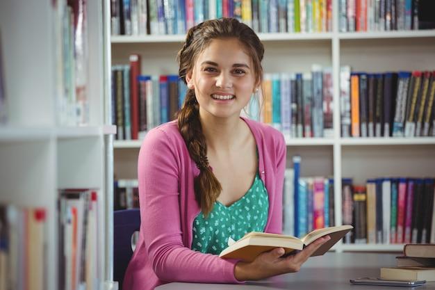 Portret uśmiechniętej uczennicy czytelnicza książka w bibliotece