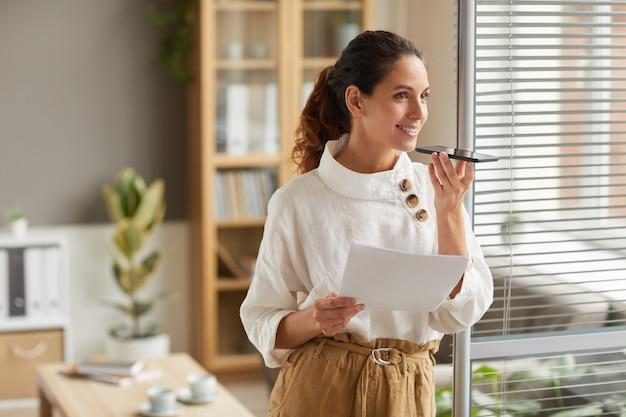 Portret uśmiechniętej udanej bizneswoman nagrywa wiadomość głosową za pomocą smartfona, stojąc przy oknie w miejscu pracy