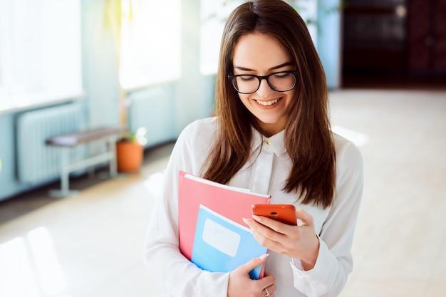 Portret uśmiechniętej uroczej dziewczyny pisać na maszynie wiadomość na telefonie komórkowym