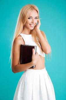 Portret uśmiechniętej uroczej kobiety trzymającej książkę na białym tle na niebieskim tle