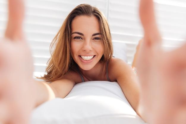 Portret uśmiechniętej uroczej kobiety w bikini, która robi zdjęcie selfie na smartfonie na białym tle