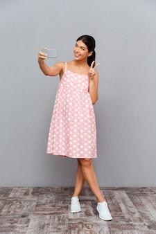 Portret uśmiechniętej uroczej kobiety w różowej sukience, która robi zdjęcie selfie na smartfonie na szarej ścianie