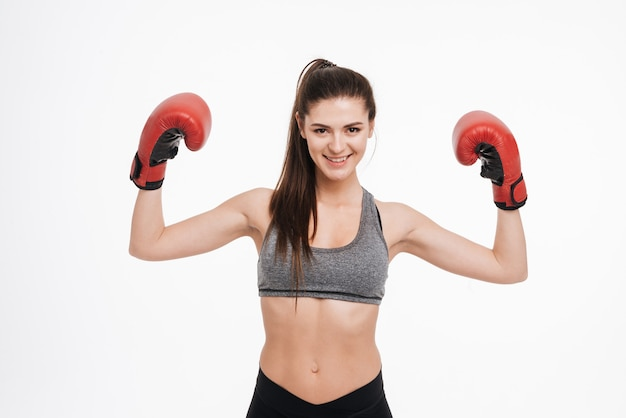 Portret uśmiechniętej zadowolonej sportowej kobiety noszącej rękawice bokserskie i pokazującej bicepsy na białym tle