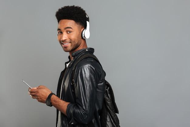 Portret uśmiechnięty afro amerykański mężczyzna z plecakiem