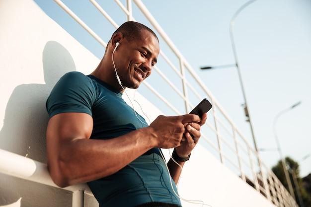 Portret uśmiechnięty afro amerykański sportowiec słucha muzyka