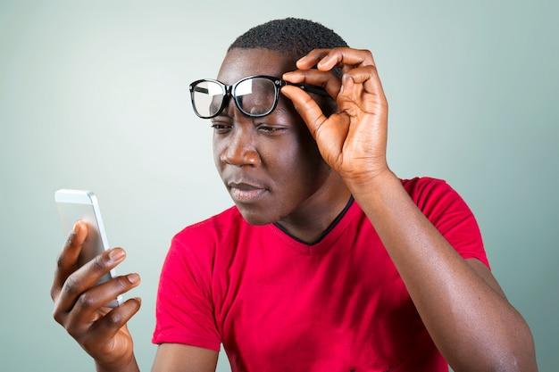 Portret uśmiechnięty afrykański młody człowiek używa smartphone