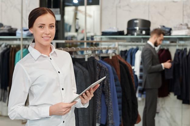Portret uśmiechnięty atrakcyjny konsultant ds. sprzedaży w białej bluzce za pomocą cyfrowego tabletu w sklepie odzieżowym